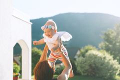 Mother throws baby up, laughing and playing in summer nature Royalty Free Stock Image