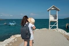 Mother and daughter summer vacation. Happy mother hold her daughter by hands at lighthouse and dock of Khao Laem Ya in Mu Ko Samet National Park, Rayong Province royalty free stock photos
