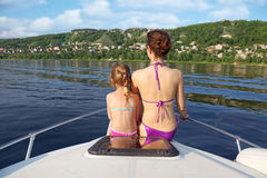 Mother daughter sunbathing on bow of cutter. Mother daughter sunbathing and talking on bow of cutter on river, back Stock Photos