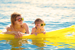 Mother and daughter on airbed. Mother and daughter in sunglasses floating on airbed together stock images