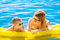 Mother and daughter on airbed. Mother and daughter in sunglasses floating on airbed together stock photography