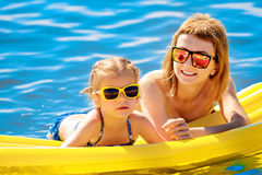 Mother and daughter on airbed. Mother and daughter in sunglasses floating on airbed together stock image