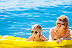 Mother and daughter on airbed. Mother and daughter in sunglasses floating on airbed together royalty free stock image