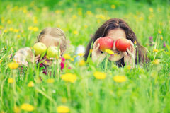 Mother and daughter on sunny meadow with apples in hands Stock Photo