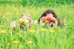 Mother and daughter on sunny meadow with apples in hands Stock Photos