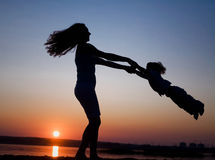 Mother and daughter on sunset. Silhouette of mother which turns the child against a sunset and water Royalty Free Stock Photos