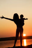 Mother and daughter on sunset. Silhouette of mother which turns the child against a sunset and water Royalty Free Stock Image
