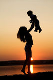 Mother and daughter on sunset. Silhouette of mother which turns the child against a sunset and water Stock Images