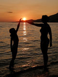Mother and daughter in sunset on beach. Mother and daughter playing with the sun on the beach Stock Photos