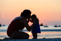 Mother and daughter on sunset beach Stock Image