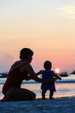 Mother and daughter on sunset beach Stock Photography