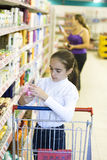 Mother and daughter in supermarket. Shopping. Girl looking for soap Royalty Free Stock Photos