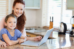Mother and daughter surfing the internet in the kitchen Royalty Free Stock Photo