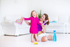 Mother and daughter sweeping the floor. Young happy mother and her little daughter, cute toddler girl, cleaning the house together sweeping the floor in a white Stock Photos