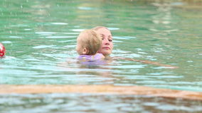 Mother and daughter swim in the pool stock video