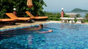 Mother and daughter swim in swimming pool