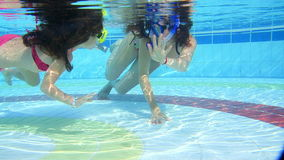 Mother and daughter swim underwater in pool.  stock video footage