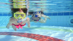 Mother and daughter swim underwater in pool.  stock video