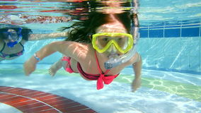 Mother and daughter swim underwater in pool.  stock footage