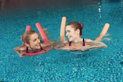 Mother and daughter swimming in pool at the gym. They look happy, fashionable and fit. royalty free stock photography
