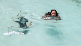 Mother and daughter swimming in pool royalty free stock photography