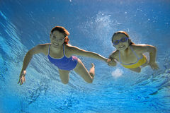 Mother and daughter (8-10) in swimming pool, smiling, portrait, underwater view Stock Photography