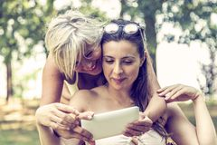 Mother and daughter in swimsuit having fun watching a digital tablet stock image