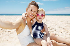 Mother and daughter in swimsuits taking selfies at beach Stock Photo