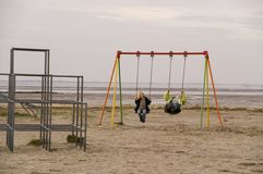 Mother and daughter on swing. Mother and daughter on beach swing with sea in background royalty free stock photos