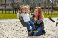 Mother and daughter in a swing at the park Royalty Free Stock Photography