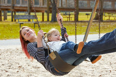 Mother and daughter in a swing at the park Stock Images