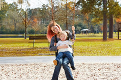 Mother and daughter in a swing at the park Royalty Free Stock Image