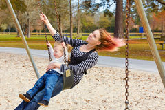 Mother and daughter in a swing at the park Royalty Free Stock Photo