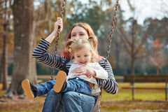 Mother and daughter in a swing at the park Stock Photo