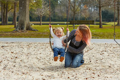 Mother and daughter in a swing at the park Royalty Free Stock Photos