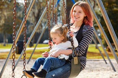 Mother and daughter in a swing at the park Stock Photos