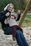 Mother and daughter swinging Stock Images
