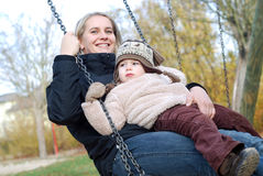 Mother and daughter swinging Royalty Free Stock Image