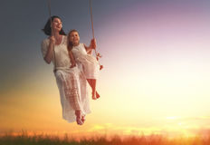 Mother and  daughter swinging on swings. Happy loving family! Young mother and her child daughter swinging on the swings and laughing a summer evening outdoors Royalty Free Stock Image