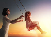 Mother and  daughter swinging on swings. Happy loving family! Young mother and her child daughter swinging on the swings and laughing a summer evening outdoors Royalty Free Stock Photo