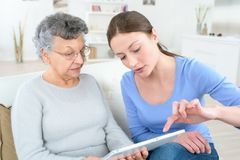 Mother and daughter with tablet computer sitting on couch Royalty Free Stock Images