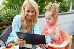 Mother and daughter with tablet pc at cafe terrace Stock Image