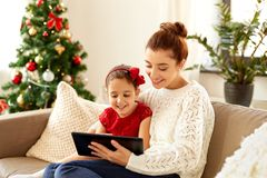 Mother and daughter with tablet pc on christmas Stock Image