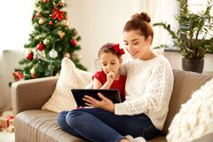 Mother and daughter with tablet pc on christmas royalty free stock photo