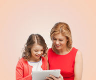 Mother and daughter with tablet pc computer. Family, child and technology concept - smiling mother and daughter with tablet pc computer Stock Photography