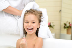 Mother and daughter taking bath. Full of positivity. Joyful little girl sitting in the bath tube while her mother during her hair with towel royalty free stock image