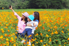 Mother and daughter taking photo in flower garden. Mother and daughter taking photo with phone selfie in flower garden royalty free stock photography