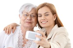 Mother and daughter taking photo of themselves. Senior mother and attractive daughter hugging each other, taking photo of themselves by digital camera, smiling Royalty Free Stock Photography