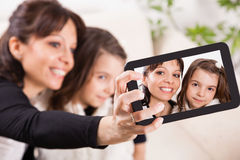 Mother and daughter taking self portraits with tablet Royalty Free Stock Photos