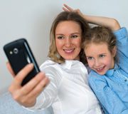 Mother and daughter taking selfie. Stock Image